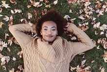 A Beautiful African American Woman Laying In A Bed Of Autumn Leaves