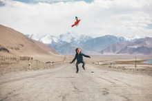 Young Boy Jumping High On A Road Looking Up To His Flying Parrot