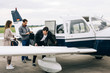 Caucasian Passengers Loading Luggage into Small Private Airplane