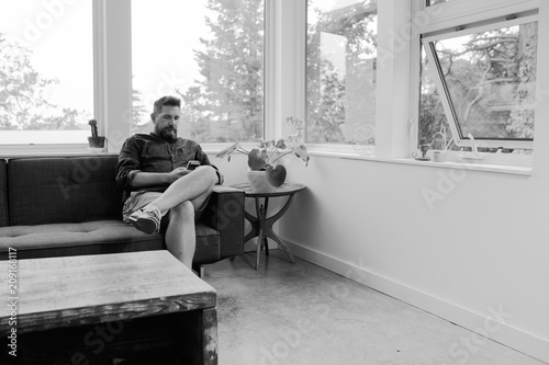 Bored and unhappy man at home wasting time on his phone