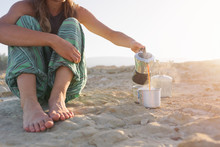 Woman Sat On The Golden Sand Pouring Coffee In A Cup