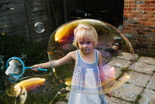 Little Girl Making Very Big Bubbles.