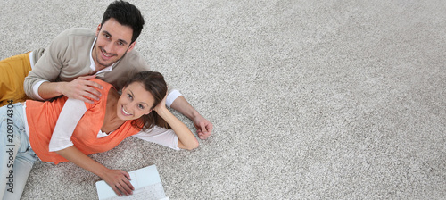 Photo Couple laying on carpet of brand new renovated flat, template