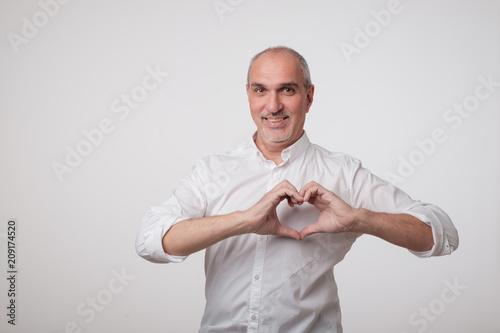 Photographie  Vieil homme européen faisant des mains le coeur