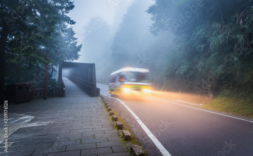Motion of fast running bus with light on local road near old bridge and walkway after sunset coverred by mist and fog inside tropical forest of Taiwan.