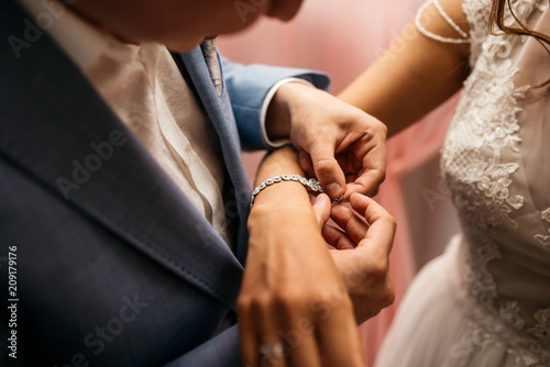 Fotografía  The groom fastens the bracelet on the bride's wrist