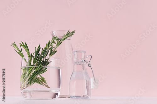 Gentle spring vanilla background of fresh bouquet rosemary in glass and retro bottles on white table and pink wall.