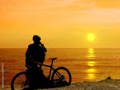Photo Boy with his bicycle resting and looking at the sea.