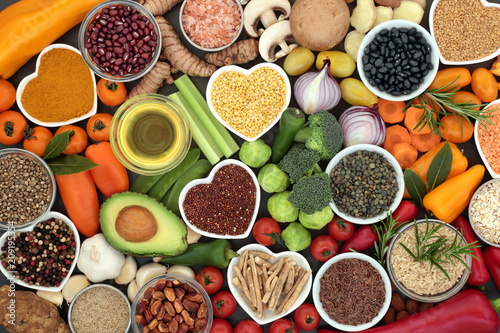 Assortiment Food for good health and fitness concept with fruit, vegetables, pulses, grains, herbs, spices, nuts, seeds, olive oil & himalayan salt. High in antioxidants, smart carbohydrates & anthocyanins.