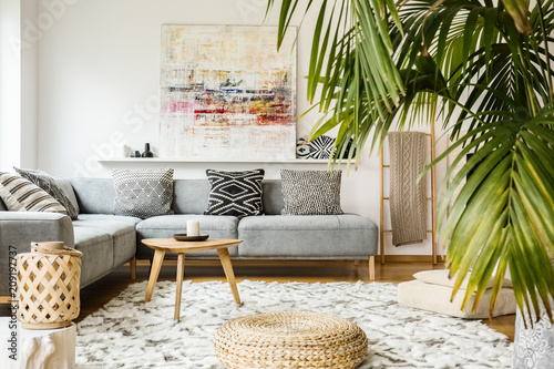 Fotografia, Obraz  Pouf and wooden table in modern living room with painting above grey corner couch