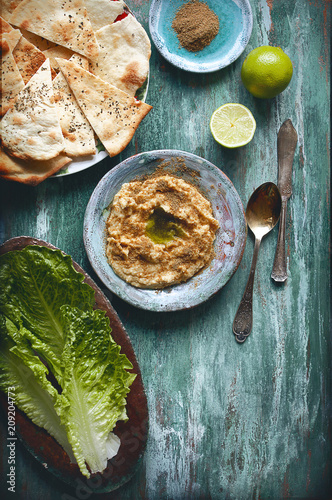 In de dag Assortiment flatlay food background - empty wooden board with hummus, salad and bread, with copy space