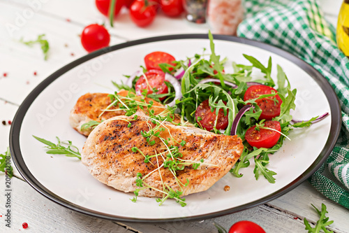 Valokuvatapetti Grilled chicken fillet and fresh vegetable salad of tomatoes,red onion and arugula