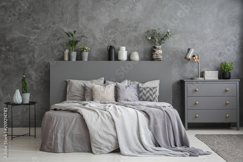 Fotobehang Sportwinkel Pillows on bed between table and cabinet in bedroom interior with concrete wall. Real photo