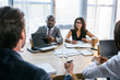 selective focus of group of multiethnic business colleagues discussing strategy during business meeting in office