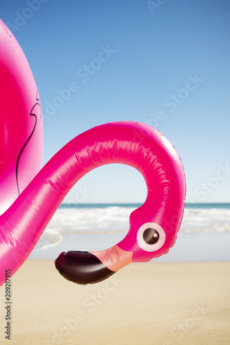 Valokuva pink flamingo swim ring on the beach