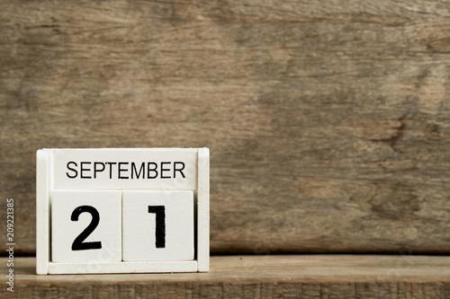Vászonkép  White block calendar present date 21 and month September on wood background