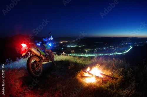 Keuken foto achterwand Fiets Motorcycle at night standing near fire flame above the valley of the Katun river view from the top hill to the bright sunset trails road