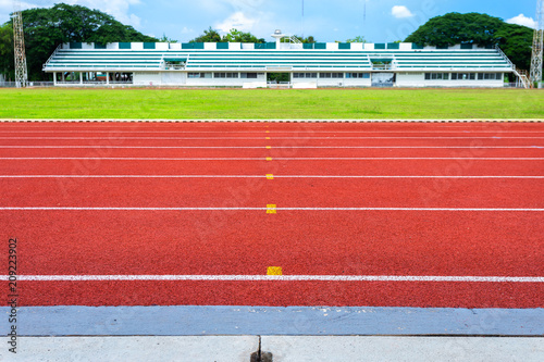 Fotomural White lines of stadium and texture of running racetrack red rubber racetracks in outdoor stadium are 8 track and green grass field,empty athletics stadium with track,football field, soccer field