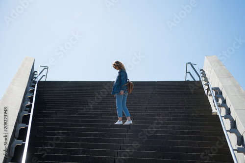 side view of woman standing on steps with blue sky on background in copenhagen, Poster