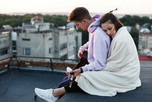 Girl Hugs Her Man Tender Sitting On The Rooftop In The Evening