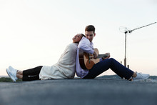 Man Plays A Guitar While His Woman Leans To Him Tender On The Rooftop