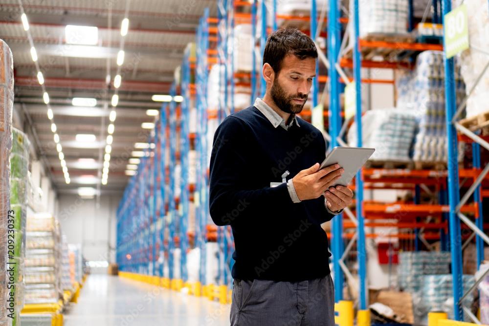 Fototapeta Manager of warehouse holding digital tablet