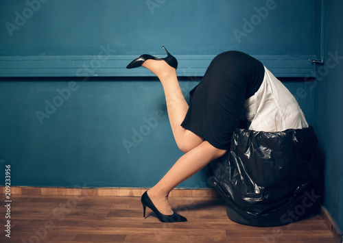 Fotografiet  Woman trying to get her head out of garbage basket