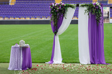 The Decorative Arch Of Violet Color, For A Ceremony Of A Solemn Wedding Is Installed On The Football Field Of Stadium.