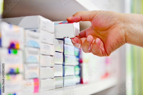 Closeup pharmacist hand holding medicine box in pharmacy drugstore.