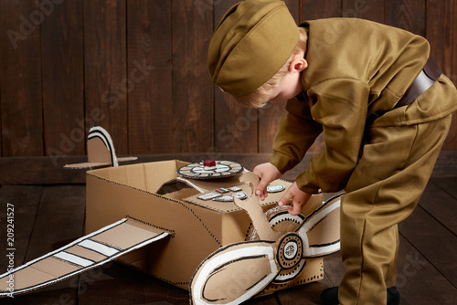 Fotografie, Obraz  children boy are dressed as soldier in retro military uniforms repair an airplan