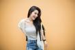 lifestyle fashion portrait of young stylish hipster Asia woman on orange background