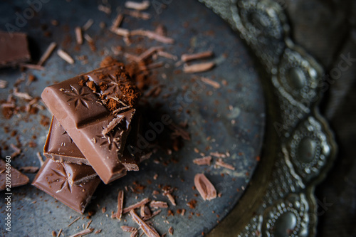 Fotobehang Eten Pieces of chocolate and cacao's dust on a vintage plate.