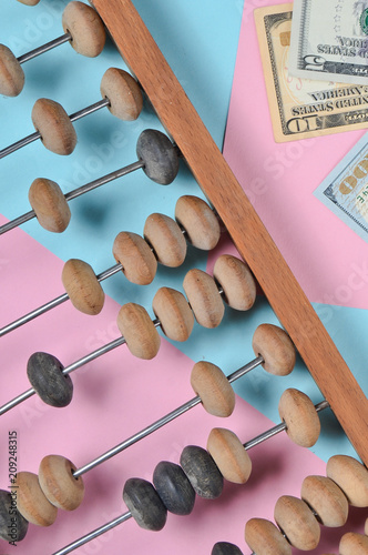 Retro wooden abacus, dollar bills on a colored paper background. top view. - 209248315