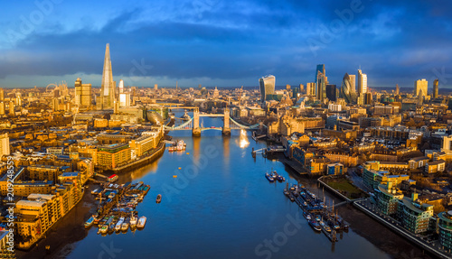 Papiers peints Vue aerienne London, England - Panoramic aerial skyline view of London including iconic Tower Bridge with red double-decker bus, skyscrapers of Bank District and other famous skyscrapers at golden hour