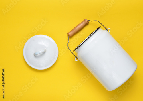 Cuadros en Lienzo Enameled milk can on yellow pastel background. Top View.
