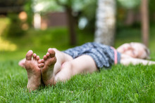 Girl Lying On The Grass, Dirty Feet On Foreground