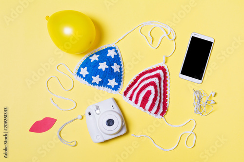 Spoed Foto op Canvas Verenigde Staten Flat lay of summer object and American flag crochet bikini top. High angle view, yellow background, studio lighting