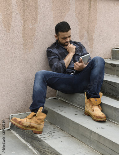 Fotografie, Obraz  young man sitting on stairs with a tablet computer