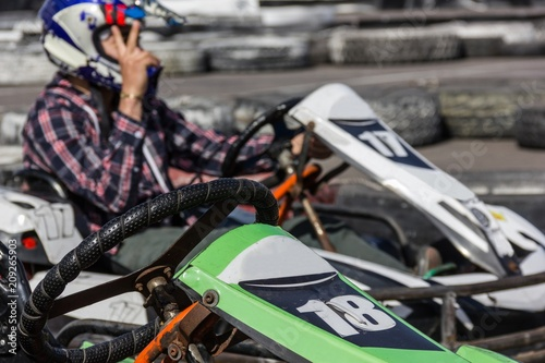 Fotografía  Green kart and unfocused man driving on circuit with hand in sign of victory
