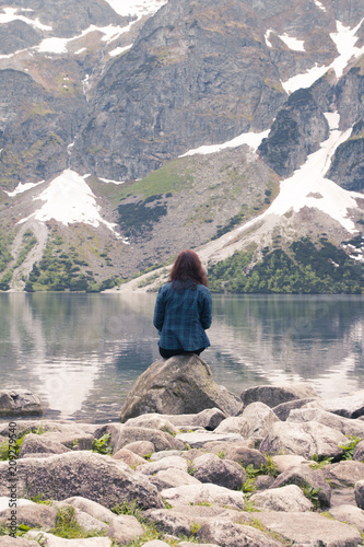 Keuken foto achterwand Olijf Young lonely brunette girl sitting on the shore of a blue lake in the mountains