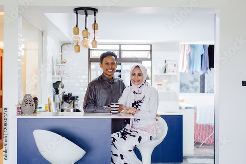 Cuadros en Lienzo  A young Muslim Malay couple sit at a table top counter and enjoy a coffee early in the morning when they break fast