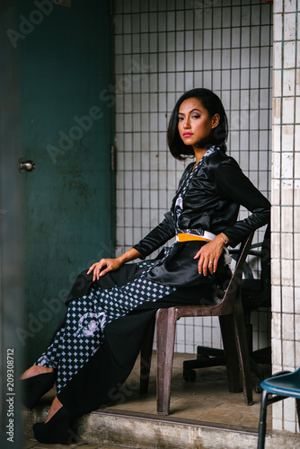 Fotografía  Fashion portrait of a young, slim, attractive and fashionable Muslim Malay woman sitting and posing on a chair in a city in Asia