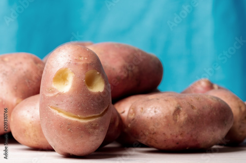 Fotografie, Obraz  potato face on red potatoes, usefulness of vegetables and affordable vegetables