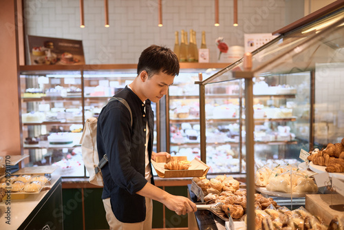 Ingelijste posters Bakkerij Handsome asian man choosing bakery in store