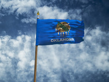 Oklahoma Flag USA Flag Silk Waving Flag Made Transparent Fabric Of Oklahoma US State With Wooden Flagpole Gold Spear On Background Sunny Blue Sky White Smoke Clouds Real Retro Photo 3d Illustration