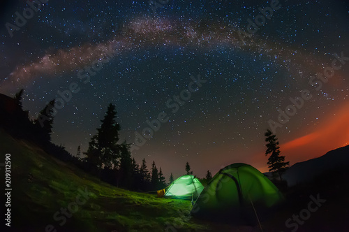Foto op Aluminium Nacht night photo in the mountains. Tents in the clearing under the starry sky, the milky way to the whole sky above the tents and mountains.