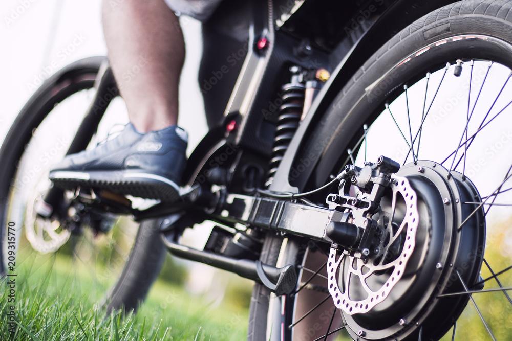 Fototapeta Man biker sitting on electric bike