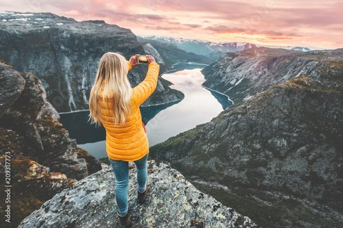 Papiers peints Gris Woman taking photo by smartphone on mountain cliff over lake traveling in Norway adventure lifestyle active vacations modern technology connection concept