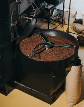 Industrial Coffee Roaster With Large Paper Bags Filled With Coffee Beans