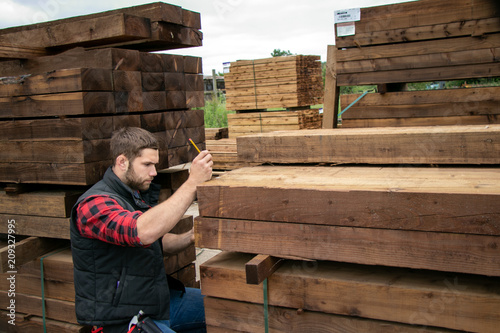 Obraz Lumber yard worker, carpenter at wood yard counts inventory with mobile device - fototapety do salonu